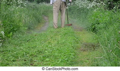 farmer man trim grass - worker man farmer cut grass in...