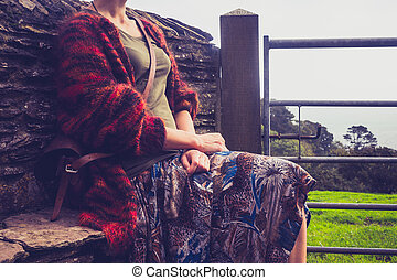 Woman relaxing by rural stone wall