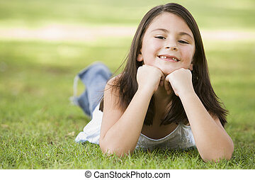 Young girl outdoors lying in grass and smiling (selective focus)