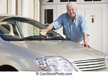 Senior man washing his car outside his home