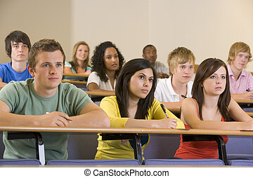 Students in class paying attention and taking notes (depth...