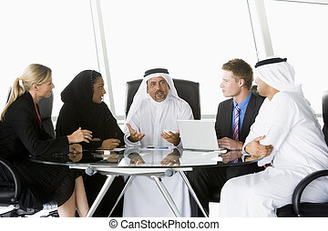 Five businesspeople in office with laptop talking and...