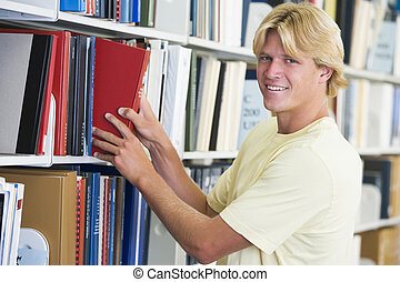 Man in library pulling book off a shelf depth of field