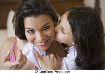 Young girl kissing smiling woman on cheek in bedroom...