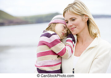 Mother holding sleeping daughter at beach