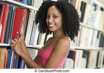 Woman in library pulling book off a shelf depth of field