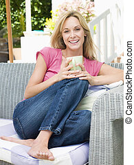 Woman sitting outdoors on patio with coffee smiling