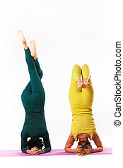senior and younger woman practice yoga - senior woman and...