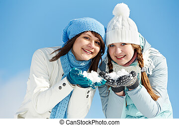 Young couple in winter - Two girl having fun with snow in...
