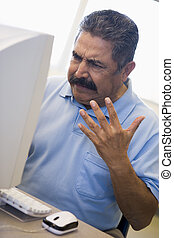 Man at computer looking at monitor frustrated (high key)