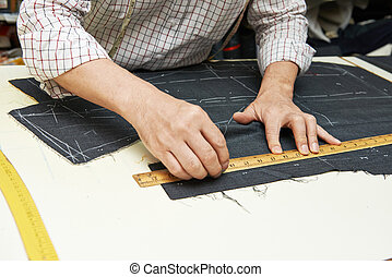 Tailor hands at works - Tailor hands working with measure...