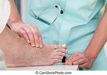 Foot massage - A doctor massaging a patient's ill foot
