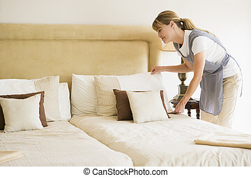Maid making bed in hotel room smiling
