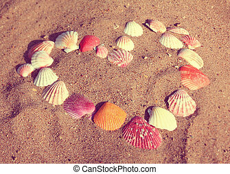 heart symbol from shells on sand - vintage retro style -...