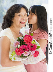 Granddaughter kissing grandmother on cheek holding flowers...