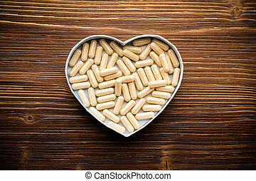 Pill. - Pill, heart-shaped box. Wooden surface.