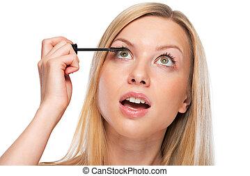 Portrait of teenage girl applying mascara