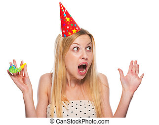 Portrait of surprised teenage girl in cap with party horn...