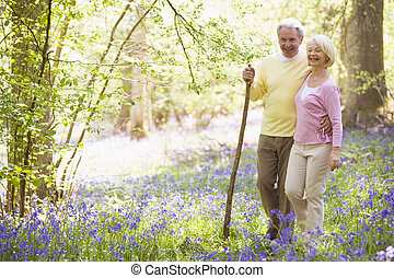 Couple walking outdoors with walking stick smiling