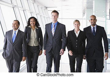 Group of co-workers walking in office space smiling (high key)
