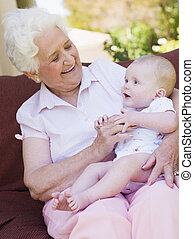 Grandmother outdoors on patio with baby smiling