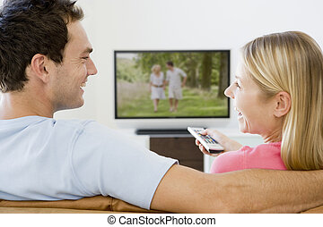 Couple in living room watching television smiling