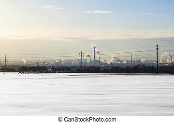 snow covered field and smoking chimneys at the horizon
