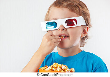 Little boy in stereo glasses eating popcorn on white...