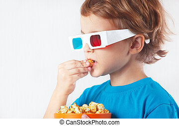Young ironic boy in stereo glasses eating popcorn on white...