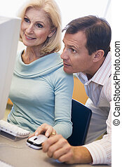 Two people at computer looking at monitor (high key)