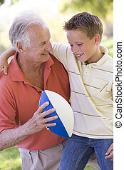 Grandfather and grandson outdoors with football smiling