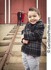 Mixed Race Boy at Train Depot with Parents Smiling Behind -...
