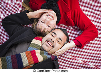 Mixed Race Couple Wearing Winter Clothing on Blanket in Park