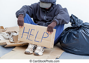 Homeless person sitting on the ground and asking for help