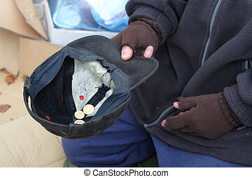 Homeless man's hand with cap for a coins