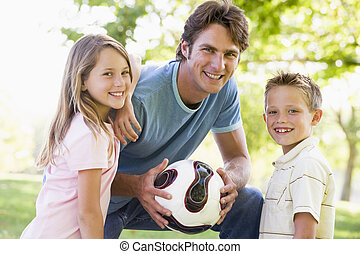 Man and two young children outdoors holding volleyball and...