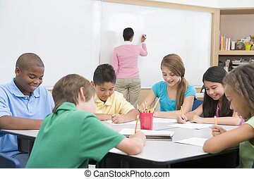 Students in class writing with teacher at front board