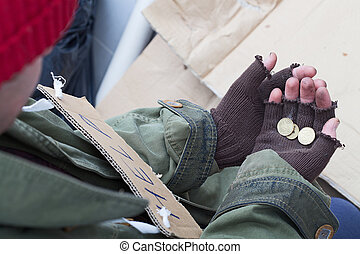 Homeless with the alms - Hands of homeless person holding a...