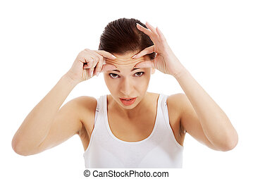 Young beautiful woman is checking her wrinkles on forehead....