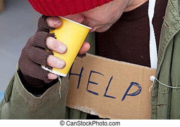 Homeless man drinking hot tea - Homeless with cardboard on...