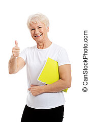 An old woman holding workbook and showing OK. Isolated on...