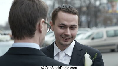 Groomsman fixing boutonniere - Groomsman fixing white...
