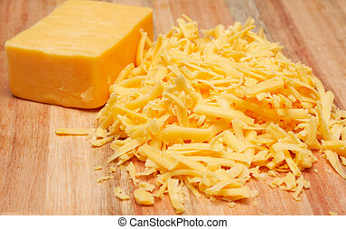 Grated cheddar cheese on wooden board