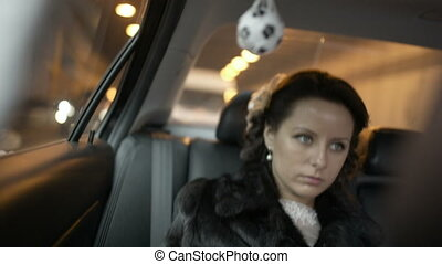 Bride in a car - Beautiful bride in fur coat traveling by...