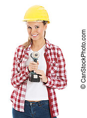 Young casual woman holding drill and wearing safety helmet...