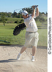 Golfer in sand bunker - Golfer hitting the ball out of the...
