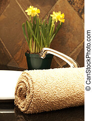 Rolled up towel and flowers in the bathroom