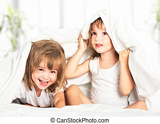happy little girls twins sister in bed under the blanket...