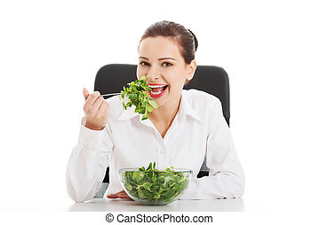 Beautiful business woman sitting and eating lettuce Isolated...
