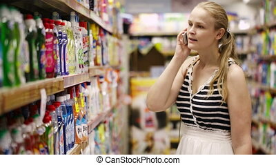 Woman chatting on her mobile while out shopping - Woman with...